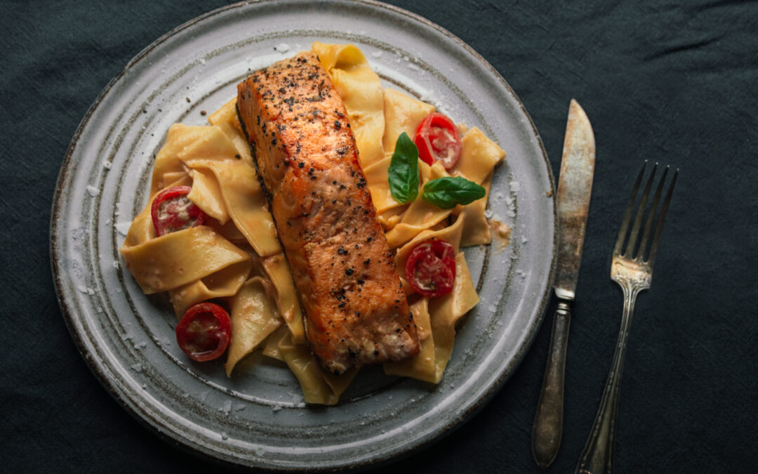 Hand-made pasta with creamy sauce and salmon fillet